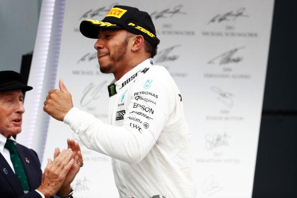 Silverstone, Northamptonshire, UK.  Sunday 16 July 2017. Winner Lewis Hamilton, Mercedes AMG, runs by Sir Jackie Stewart on the podium. World Copyright: Glenn Dunbar/LAT Images  ref: Digital Image _X4I7936