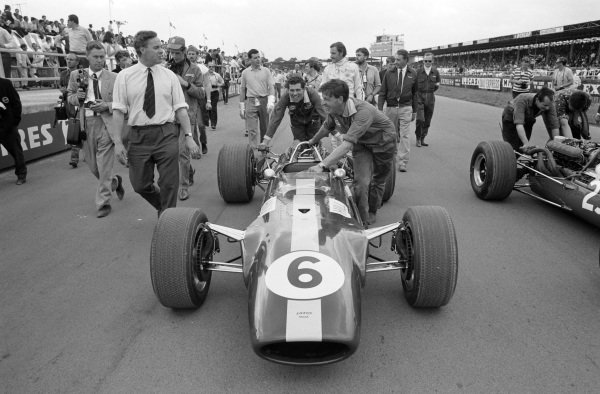 Graham Hill's Lotus 49 Ford is pushed to the grid by mechanics. Hill walks behind.