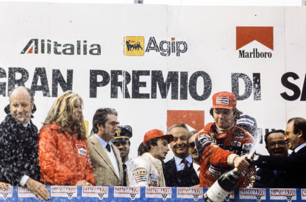 Didier Pironi, 1st position, sprays champagne while Gilles Villeneuve, 2nd position, walks away.