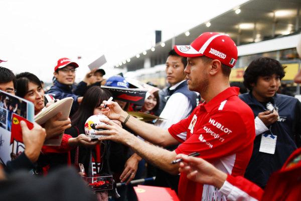 Sebastian Vettel, Ferrari, signs an autograph for a fan
