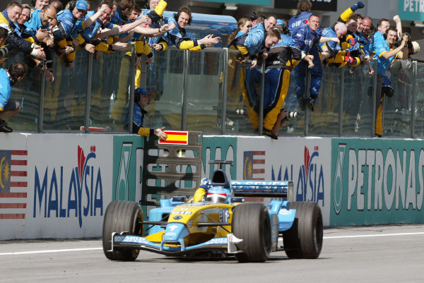 2003 Malaysian Grand Prix. Sepang, Kuala Lumpur, Malaysia.21-23 March 2003.Fernando Alonso (Renault R23) celebrates as he takes his 3rd position at the finish and the congratulations from the Renault team.World Copyright - Steve Etherington/LAT Photographic ref: Digital Image Only
