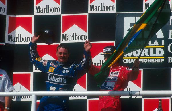 1992 Hungarian Grand Prix.Hungaroring, Budapest, Hungary.14-16 August 1992.Nigel Mansell (Williams Renault) celebrates 2nd position on the podium and winning the drivers World Championship. Ayrton Senna (McLaren Honda) 1st position also congratulates him.Ref-92 HUN 05.World Copyright - LAT Photographic