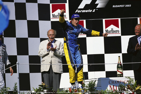 Fernando Alonso, 1st position, celebrates his first grand prix win on the podium.