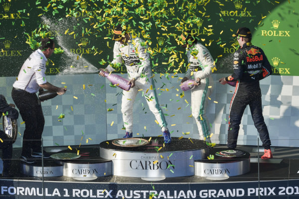 Champagne and confetti fill the air as the drivers celebrate on the podium