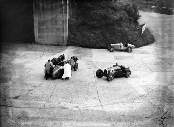 Piero Taruffi, Bugatti T51, passes officials attempting to move Malcolm Campbell's Sunbeam Tiger.  The abandoned  Bugatti T51 of Tim Rose-Richards can be seen in the background.