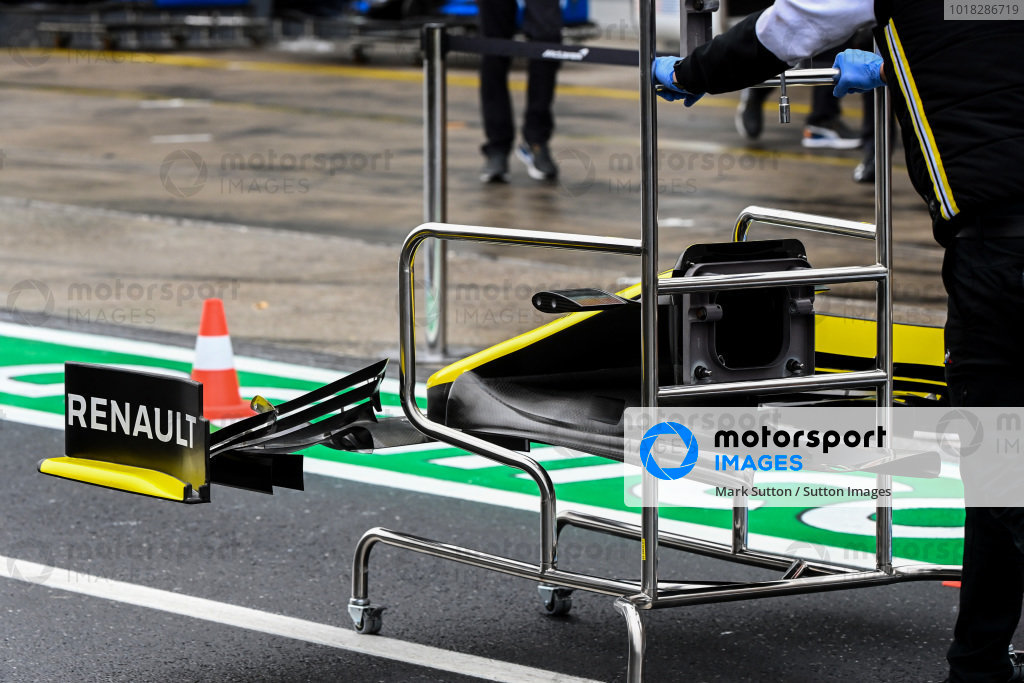 A Renault mechanic wheels a front wing through the pitlane