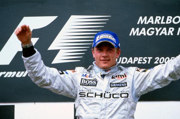 2005 Hungarian Grand Prix. Hungaroring, Hungary. 29th - 31st July 2005 Kimi Raikkonen, McLaren Mercedes MP4-20 celebrates his victory on the podium. World Copyright: Lorenzo Bellanca/LAT Photographic Ref: 35mm Image A17