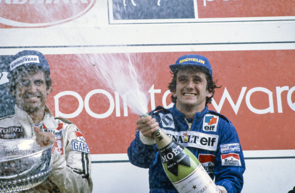 Alain Prost, 1st position, sprays champagne on the podium next to Carlos Reutemann, 2nd position.