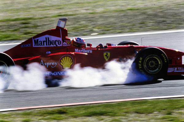 Michael Schumacher, Ferrari F310B, locks up a tyre.