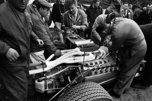 Mechanics work on Jacky Ickx's Ferrari 312, laying out their tools on the rear wing.