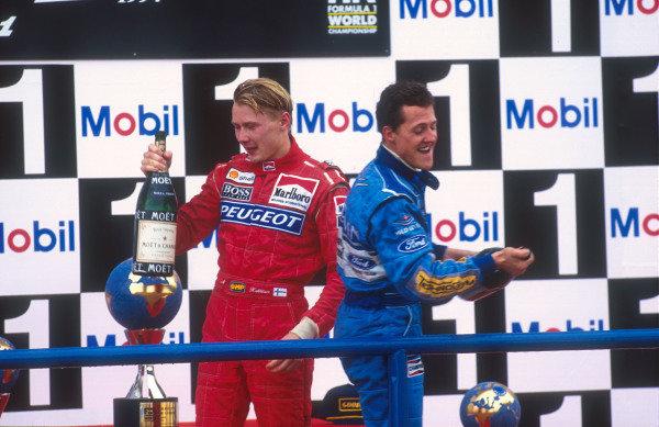 1994 European Grand Prix.Jerez, Spain.14-16 October 1994.Michael Schumacher (Benetton Ford) 1st position and Mika Hakkinen (McLaren MP4/9 Peugeot) 3rd position celebrate on the podium.Ref-94 EUR 07.World Copyright - LAT Photographic