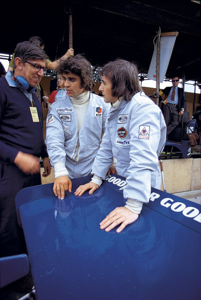 Ken Tyrrell talks to Francois Cevert and Jackie Stewart in the pit lane.