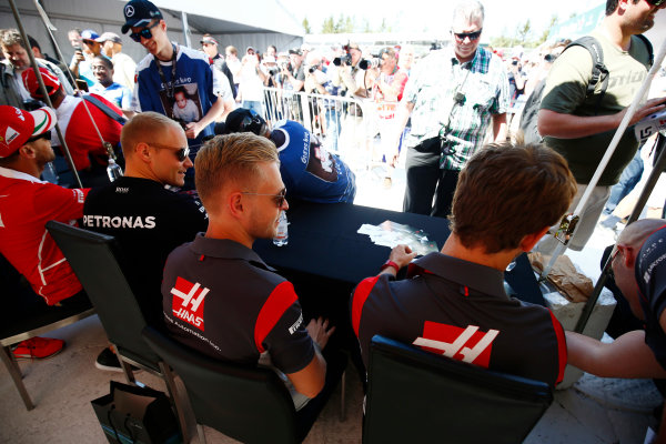 Circuit Gilles Villeneuve, Montreal, Canada. Thursday 08 June 2017. Valtteri Bottas, Mercedes AMG, signs autographs for fans alongside Kevin Magnussen, Haas F1, and Romain Grosjean, Haas F1.  World Copyright: Andy Hone/LAT Images ref: Digital Image _ONZ9914