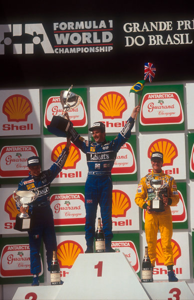 1992 Brazilian Grand Prix.Interlagos, Sao Paulo, Brazil.3-5 April 1992.Nigel Mansell, 1st position and Riccardo Patrese 2nd position (both Williams Renault) with Michael Schumacher (Benetton Ford) 3rd position on the podium.Ref-92 BRA 06.World Copyright - LAT Photographic