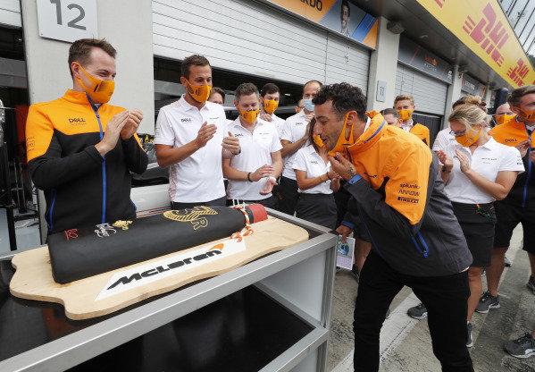 Lando Norris, McLaren and team members with Daniel Ricciardo, birthday cake in pit lane garage