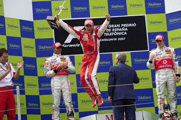 Felipe Massa leaps off the top step off the podium with his winner's trophy in hand. Lewis Hamilton, 2nd position, and Fernando Alonso, 3rd position, round out the podium.