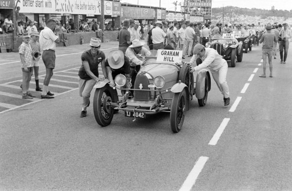 Graham Hill attempts to push his parade car into action with a little help.