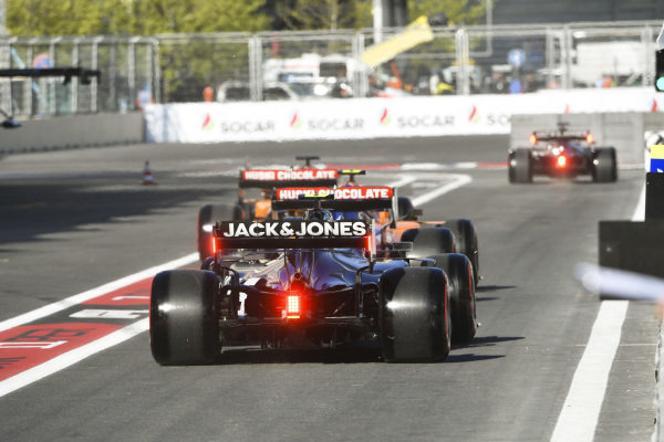 Carlos Sainz Jr., McLaren MCL34, leads Lando Norris, McLaren MCL34, and Kevin Magnussen, Haas VF-19, out of the pits