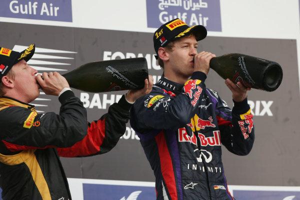 Bahrain International Circuit, Sakhir, Bahrain Sunday 21st April 2013 Sebastian Vettel, Red Bull Racing, 1st position, and Kimi Raikkonen, Lotus F1, 2nd position, drink Waard on the podium. World Copyright: Andy Hone/LAT Photographic ref: Digital Image HONZ3084
