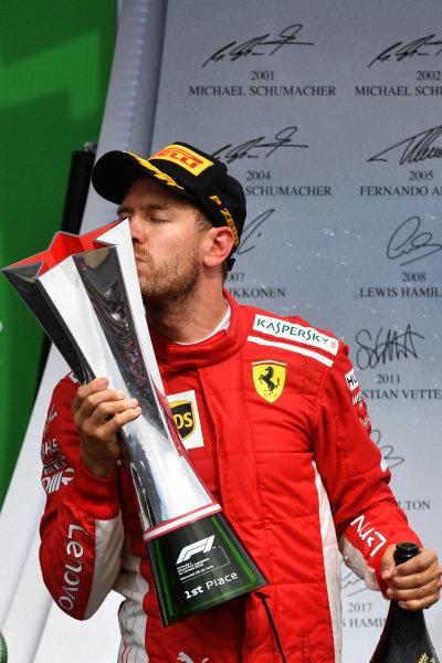 Race winner Sebastian Vettel (GER) Ferrari celebrates on the podium and kisses the trophy .