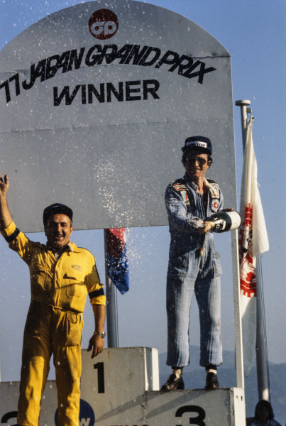 Patrick Depailler and a mechanic celebrate third place on the podium alone as winner James Hunt and second place Carlos Reutemann had already left the circuit to catch a flight.
