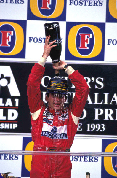 Ayrton Senna, 1st position, pours champagne over himself on the podium.