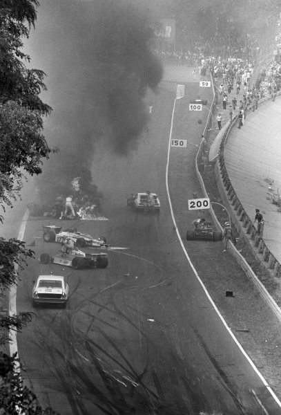 The immediate aftermath of the multi-car accident at the start of the race: James Hunt (GBR) McLaren attempts to pull Ronnie Peterson (SWE) from his burning Lotus79. Tragically, Peterson would die from a blood clot following an operation in hospital on his badly broken legs. Other drivers stopped include Clay Regazzoni (SUI) Shadow DN9, Patrick Tambay (FRA) McLaren M26 and Vittorio Brambilla (ITA) Surtees TS20 (Right), who suffered a severe head injury in the accident. Italian Grand Prix, Rd14, Monza, Italy, 10 September 1978.