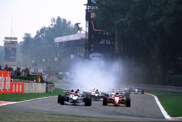 1995 Italian Grand Prix.Monza, Italy.8-10 September 1995.Michael Schumacher (Benetton B195 Renault) and Gerhard Berger (Ferrari 412T2) lead at the start.World Copyright - LAT Photographic