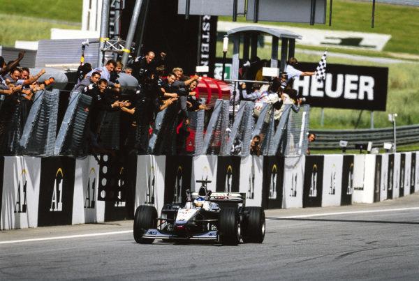 Mika Häkkinen, McLaren MP4-15 Mercedes, celebrates as he crosses the line to take victory.