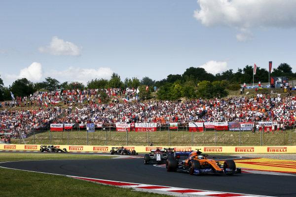 Lando Norris, McLaren MCL34, leads Kimi Raikkonen, Alfa Romeo Racing C38, and Pierre Gasly, Red Bull Racing RB15