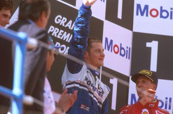 Estoril, Portugal.20-22 September 1996.Jacques Villeneuve (Williams Renault) 1st position celebrates on the podium alongside teammate Damon Hill and Michael Schumacher (Ferrari).Ref-96 POR 01.World Copyright - LAT Photographic