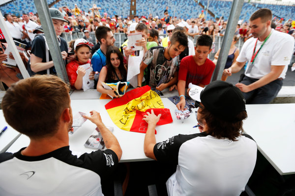 Hungaroring, Budapest, Hungary. Thursday 23 July 2015. Jenson Button, McLaren, and Fernando Alonso, McLaren, sign autographs for fans. World Copyright: Charles Coates/LAT Photographic ref: Digital Image _N7T1967