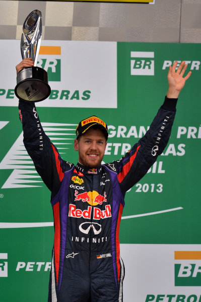 Race winner Sebastian Vettel (GER) Red Bull Racing celebrates with the trophy on the podium. Formula One World Championship, Rd19, Brazilian Grand Prix, Race, Sao Paulo, Brazil, Sunday 24 November 2013.