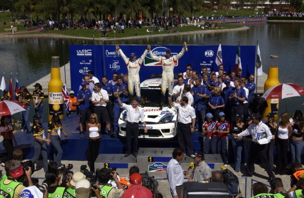 The rally winning crew of Michael Park (GBR) and Markko Martin (EST) Ford Focus RS WRC 03 celebrate victory on the podium with Malcolm Wilson (GBR) Ford Team Boss.World Rally Championship, Rd3, Rally Mexico, Leon, Mexico. Day Three. 14 March 2004.DIGITAL IMAGE
