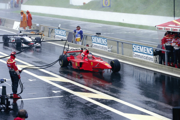 Michael Schumacher, Ferrari F300, with missing front wheel and wing, and David Coulthard, McLaren MP4-13 Mercedes, with missing rear wing, return to the pits after their crash.