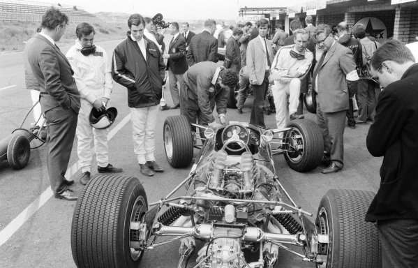 Jackie Stewart, Chris Irwin, Mike Spence and Tony Rudd are among those examining the new Lotus 49 Ford in the pit lane.