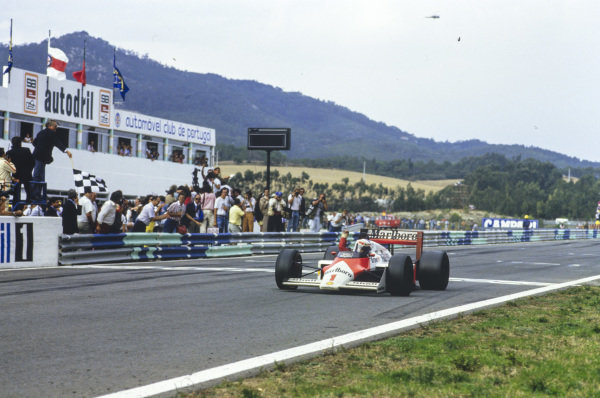 Alain Prost, McLaren MP4-3 TAG, raises an arm as he takes the chequered flag, and applause from the pit wall, at the finish. The result gave Prost a record 28 grand prix wins, surpassing Jackie Stewart's long-standing previous record of 27.