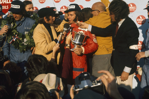 Jackie Stewart interviews Emerson Fittipaldi on the podium after winning his second world championship. Race winner Carlos Reutemann is interviewed on the left.