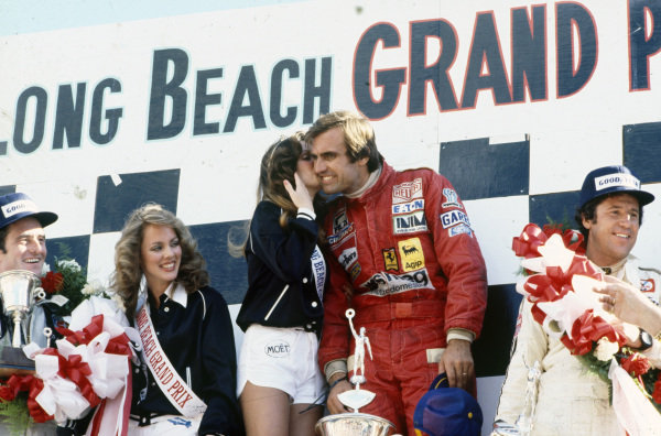 Winner Carlos Reutemann celebrates victory on the podium with a kiss from Miss Long Beach Grand Prix. Mario Andretti, 2nd position, and Patrick Depailler, 3rd position, stand either side.