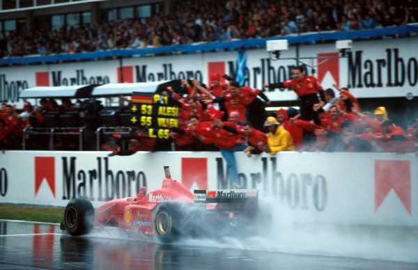 Race winner Michael Schumacher (GER) Ferrari F310 takes the adulation of his team from the pit wall at the end of the race. Spanish Grand Prix, Barcelona, Spain, 2 June 1996.