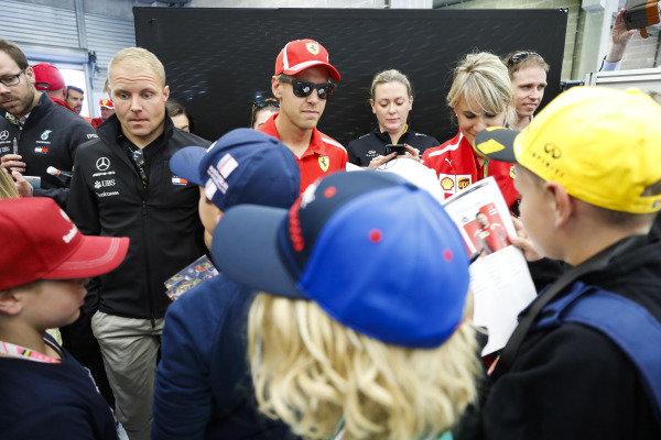 Valtteri Bottas, Mercedes AMG F1, and Sebastian Vettel, Ferrari, sign autographs for children.