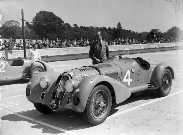 H. C. Hunter stands next to his Alfa Romeo on the grid.