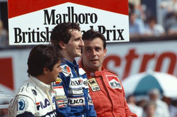 1983 British Grand Prix. Silverstone, England. 14-16 July 1983. Alain Prost (Equipe Renault) 1st position, Nelson Piquet (Brabham BMW) 2nd position and Patrick Tambay (Ferrari) 3rd position on the podium. Ref-83 GB 16. World Copyright - LAT Photographic