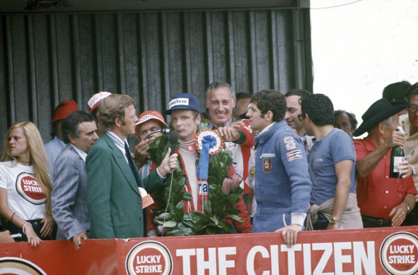 Niki Lauda is interviewed on the podium after claiming victory. Jody Scheckter, 2nd position, stands to the right.