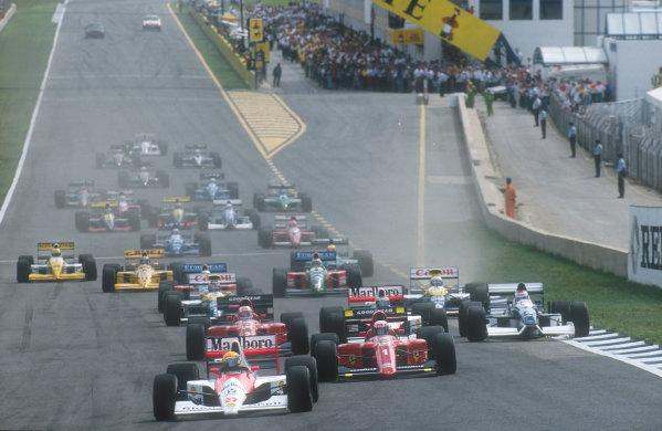 1990 Spanish Grand Prix.Jerez, Spain.28-30 September 1990.Ayrton Senna (McLaren MP4/5B Honda) leads Alain Prost, Nigel Mansell (both Ferrari 641's), Gerhard Berger (McLaren MP4/5B Honda), Jean Alesi (Tyrrell 019 Ford)(note punctured tyre, his left rear), Riccardo Patrese, Thierry Boutsen (both Williams FW13B Renault's), Alessandro Nannini and Nelson Piquet (both Benetton B190 Ford's) at the start.Ref-90 ESP 15.World Copyright - LAT Photographic
