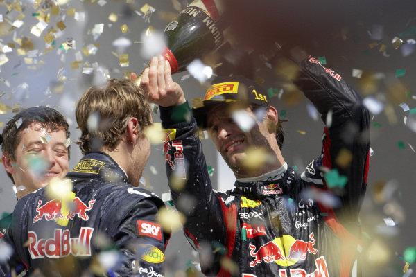 Mark Webber, 1st position, celebrates on the podium with Sebastian Vettel, 2nd position, and Will Courtney.