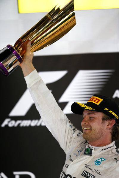 Yas Marina Circuit, Abu Dhabi, United Arab Emirates. Sunday 29 November 2015. Nico Rosberg, Mercedes AMG, 1st Position, lifts his trophy on the podium. World Copyright: Charles Coates/LAT Photographic ref: Digital Image _99O2669