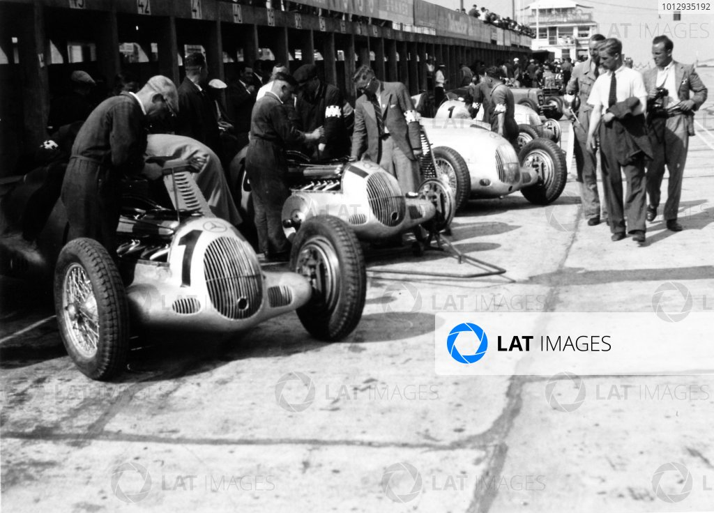1936 Eifelrennen.Nurburgring, Germany. 14 June 1936.The Mercedes-Benz W25C of Rudolf Caracciola, Manfred von Brauchitsch, Hermann Lang, Luigi Fagioli and Louis Chiron in the pits. The voiturette ERA's of Raymond Mays and Earl Howe are in the distance, atmosphere.World Copyright: Robert Fellowes/LAT PhotographicRef: 36EIF04