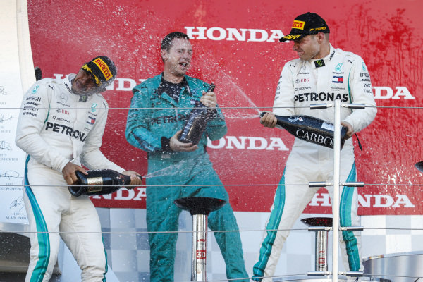 Lewis Hamilton, Mercedes AMG F1, 1st position, and Valtteri Bottas, Mercedes AMG F1, 2nd position, spray Champagne with their team mate on the podum