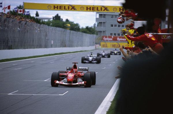 Michael Schumacher, Ferrari F2003-GA, leading Ralf Schumacher, Williams FW25 BMW, Juan Pablo Montoya, Williams FW25 BMW, and Fernando Alonso, Renault R23, across the finish line at the end of the race.